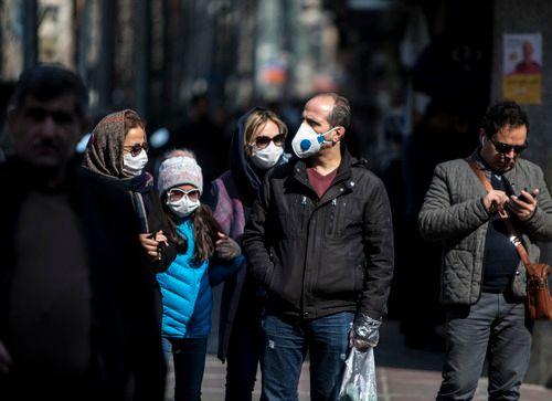 2月23日,伊朗首都德黑兰街头,一些市民戴上口罩。新华社发