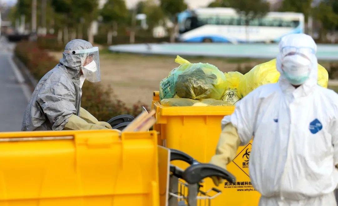 一名后勤人员正在转运从医院楼内清理出来的医疗废物卸车,他每天工作在12个小时左右。(摄影:崔萌)