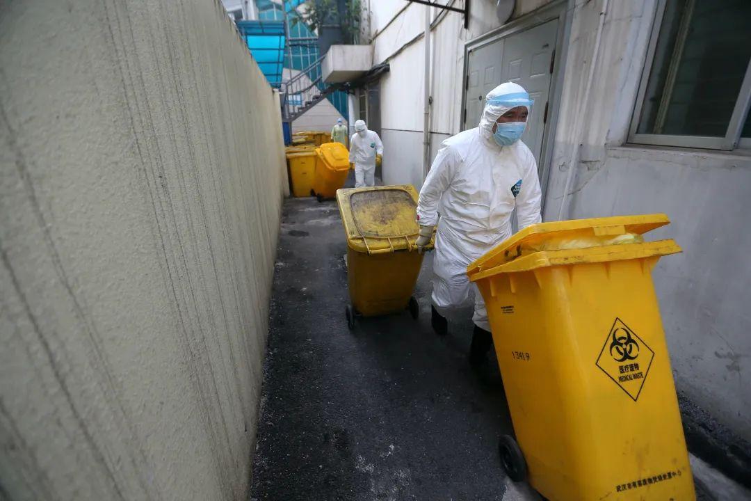 武汉市红十字会医院,后勤人员在清晨把提前装桶的医疗废物拖出准备装车转运。由于量太大,多个省市有医疗废物处置资质的队伍驰援武汉,义务协助医院转运。(摄影:崔萌)