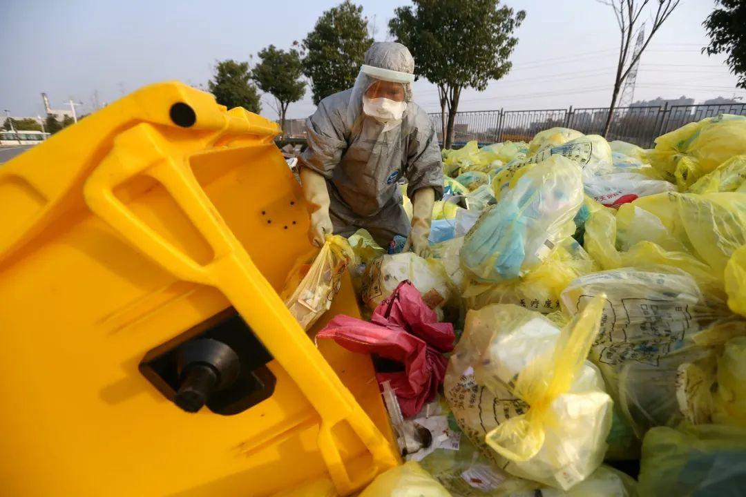 一名负责清运医院大楼内医疗废物的工人正在从垃圾车里取出废物袋堆放在户外临时存放点。这些医疗废物大都污染严重,包括用过的防护服、手套、口罩、医疗用具甚至病患的呕吐物等。(摄影:崔萌)