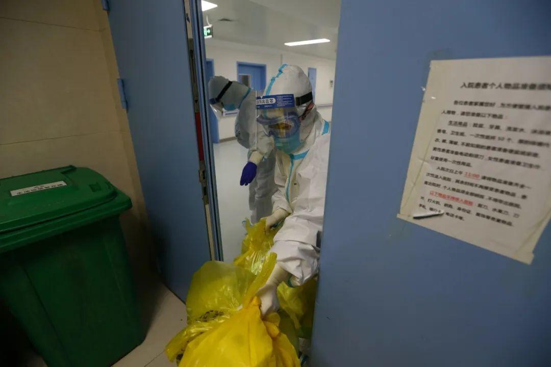 清晨,一名护士将夜里产生的医疗废物送出重症隔离区。(摄影:崔萌)