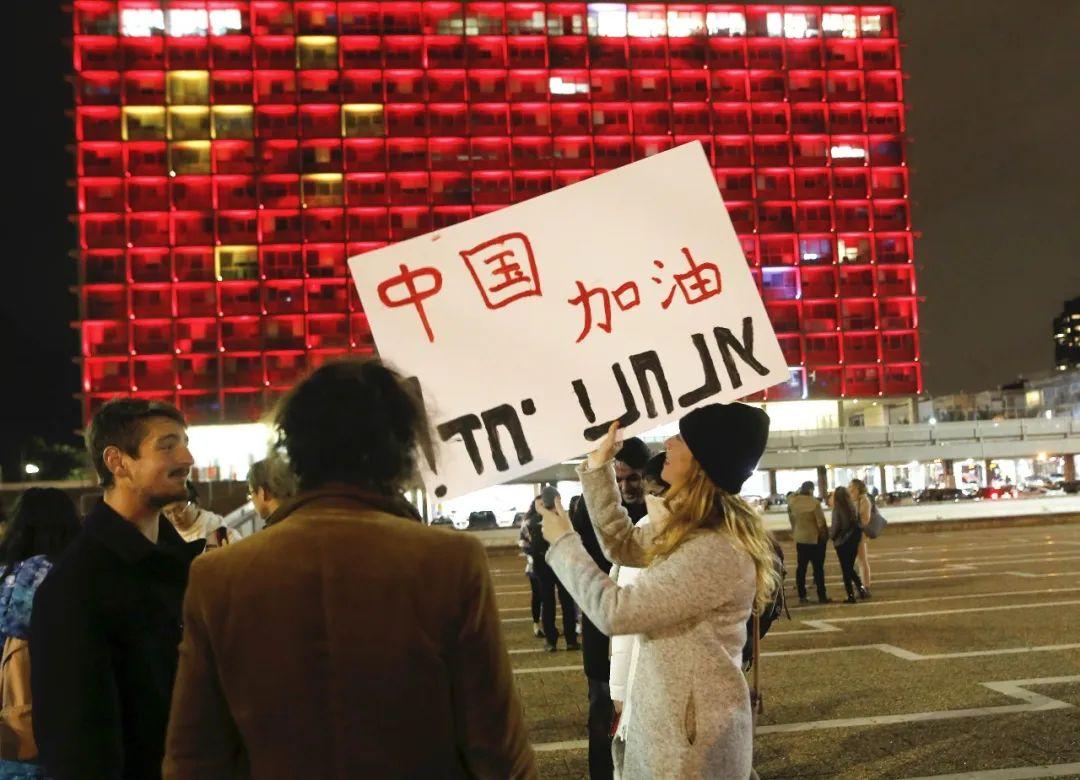 """2月11日,在以色列特拉维夫市政大楼前,一名女子手举带有""""中国加油""""字样的宣传板,宣传板上用希伯来语写着""""我们在一起""""。新华社发(吉尔·科恩·马根摄)"""