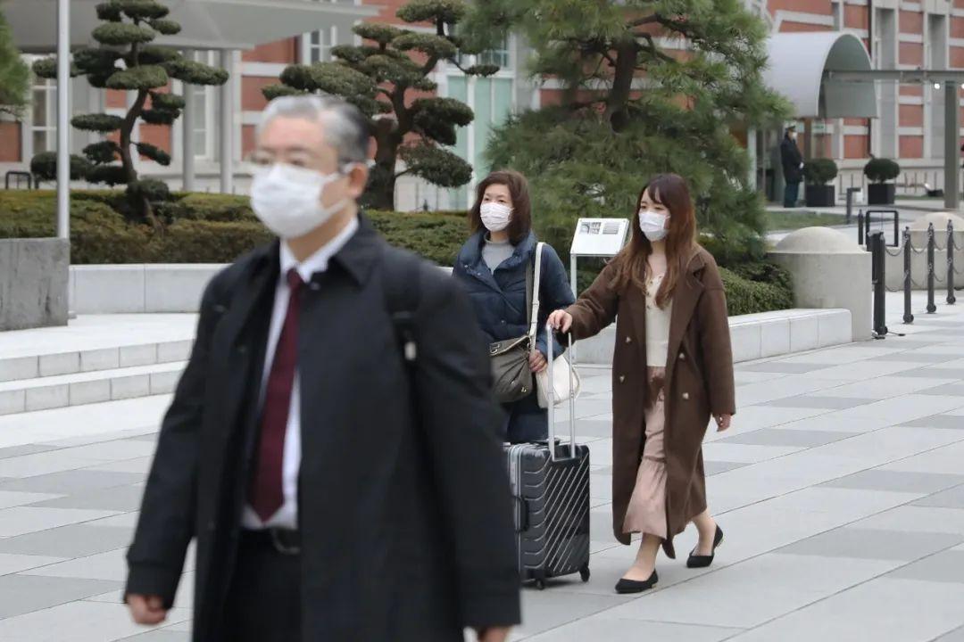 2月25日,在日本东京,人们戴口罩出行。