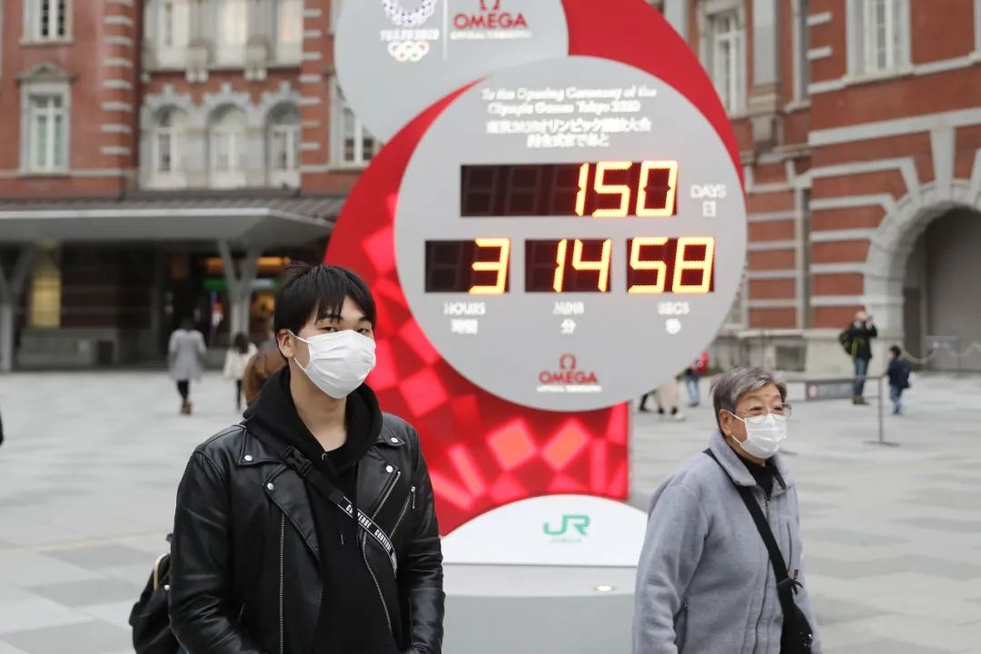 2月25日,在日本东京,行人戴口罩经过显示东京奥运会倒计时的电子屏。新华社记者 杜潇逸 摄