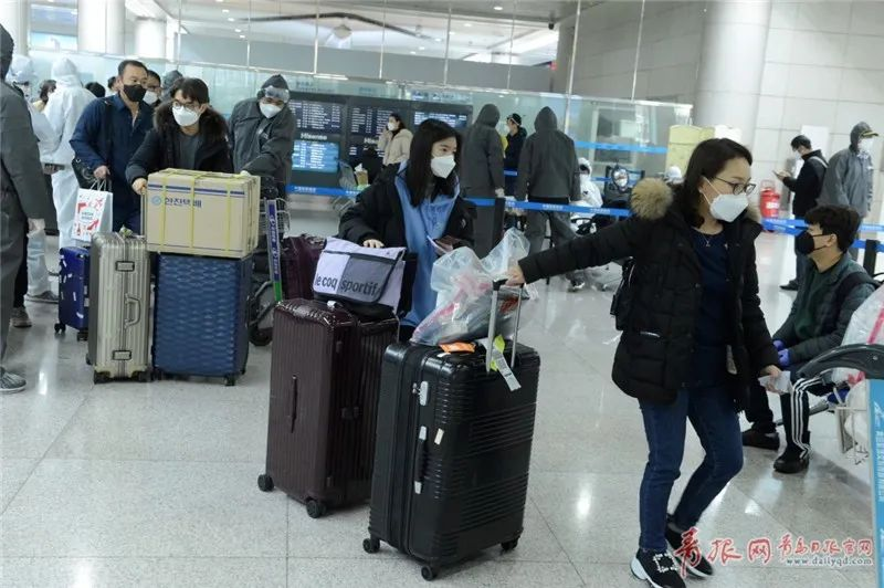 2月25日,由韩国抵达青岛流亭国际机场的乘客在完成相关登记手续后分区市离开。记者 傅学军 摄