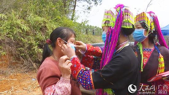 邓继妍给村民送口罩,并指导如何佩戴。上思县融媒体中心供图