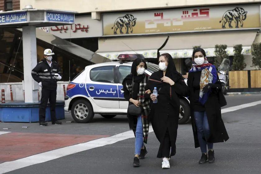 ▲2月23日,德黑兰街头,警察和行人戴上口罩。(美联社)