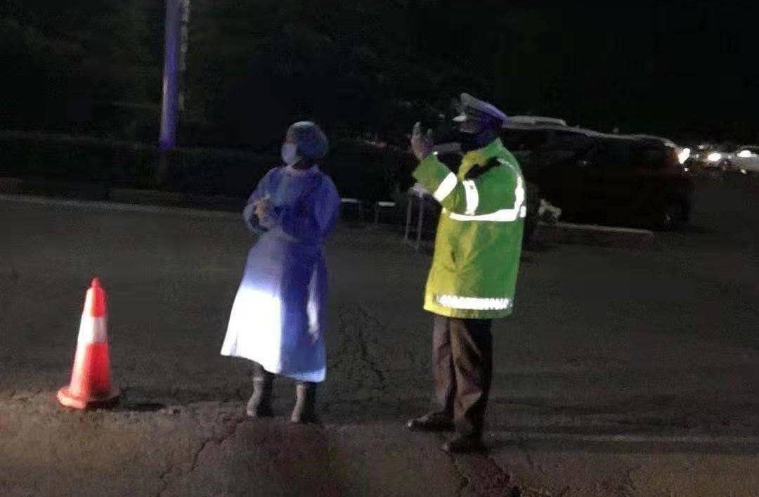 图片说明:黄珮钊和妻子夜间在公路卡点执勤
