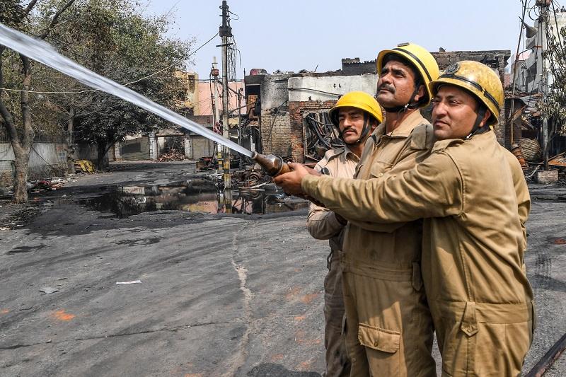△印度新德里仍然在工作中的消防人员(图片来源:印度NDTV)
