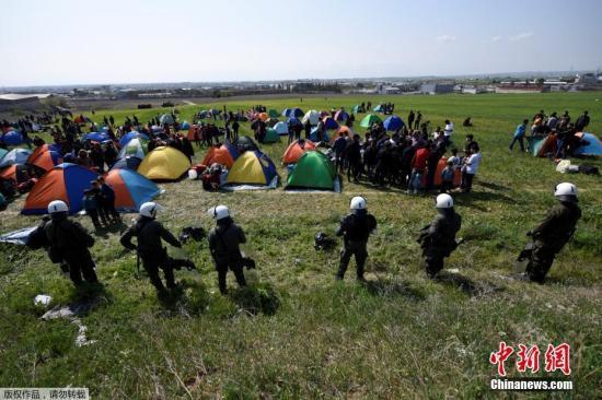资料图:希腊北部城市迪亚瓦塔的郊外,防暴警察在难民搭建的营地旁站岗。