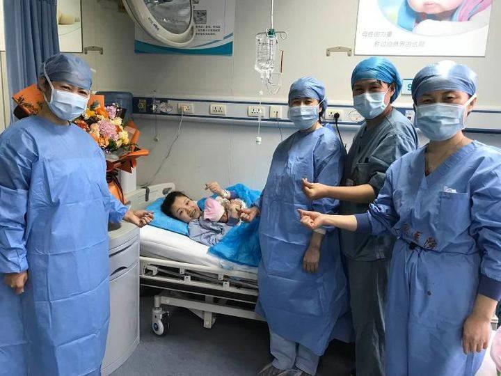 李伟妻子抱着宝宝向镜头比心