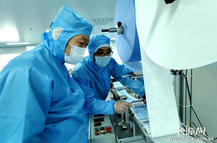 际华三五零二技能保障部人员调试平面口罩出产机械。  记者 信贺宁 摄
