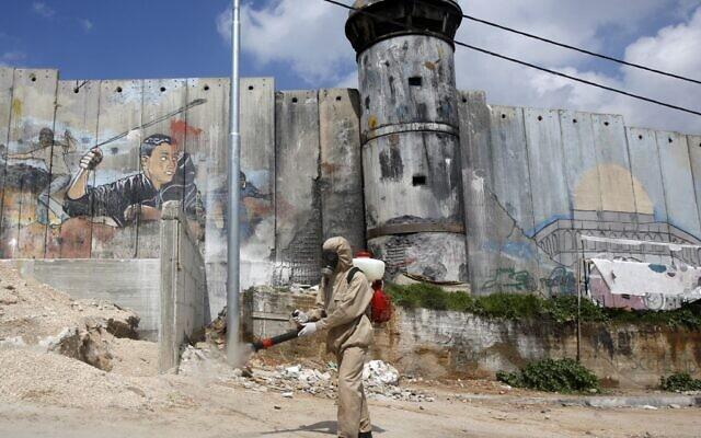 △图为一名巴勒斯坦卫生部门工作人员在伯利恒附近喷洒消毒剂 图片来源:法新社