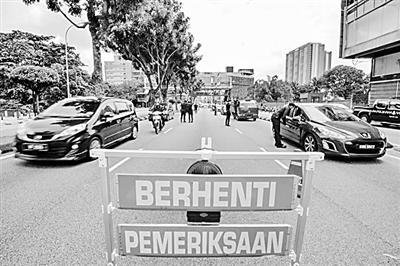 3月19日,在马来西亚吉隆坡,警察设卡检查来往车辆。马来西亚18日起在全国范围内采取为期两周的严格限制措施,禁止民众在非必要情况下外出。新华社发