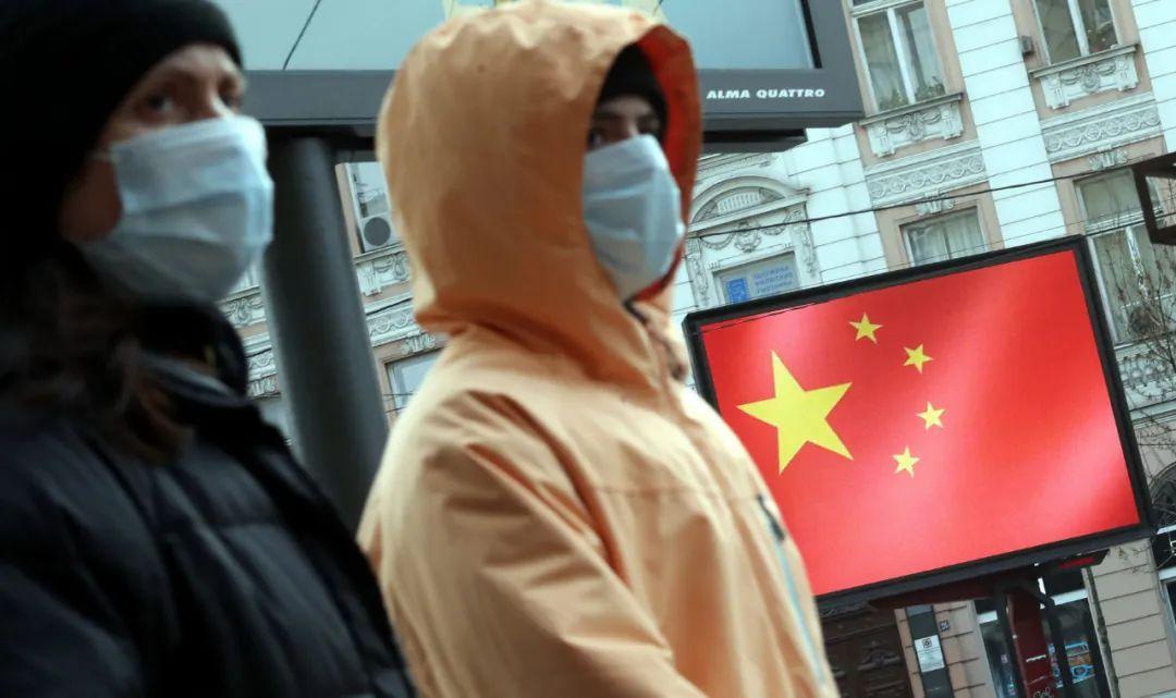 3月23日,在塞尔维亚贝尔格莱德,人们路过一处显示中国国旗的显示屏。新华社发(内马尼亚摄)