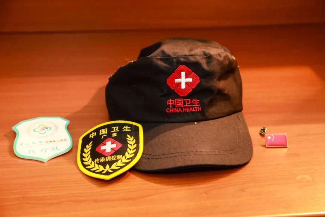 """3月24日,在塞尔维亚首都贝尔格莱德,一名中国援塞医疗专家的书桌上,放着写有""""中国卫生""""字样的帽子和臂章,以及中山大学附属第三医院医疗队的臂章和中国国旗胸章。新华社记者石中玉摄"""