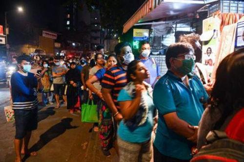 """印度总理莫迪宣布""""封城""""后,印度民众开始纷纷涌向超市和药店,购买生活和医疗必需品。(图源:BBC )"""