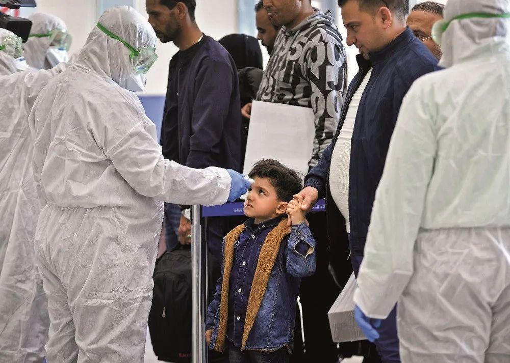 2020 年2月21日,伊朗纳杰夫国际机场,工作人员为旅客测量体温。图 / 法新