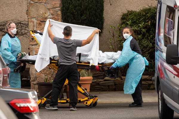 工作人员送养老院一名患者上救护车,图据《商业内幕》
