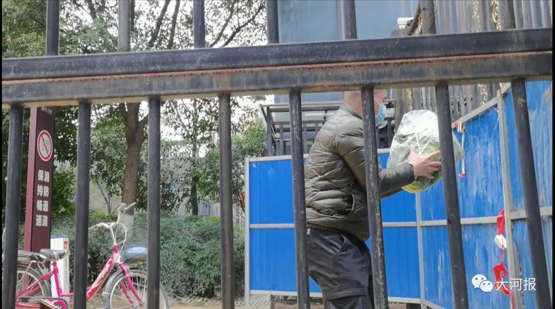 ▲业主从铁栅栏外接收外卖小哥送来的蔬菜,抱怨社区配送的菜,价高质次