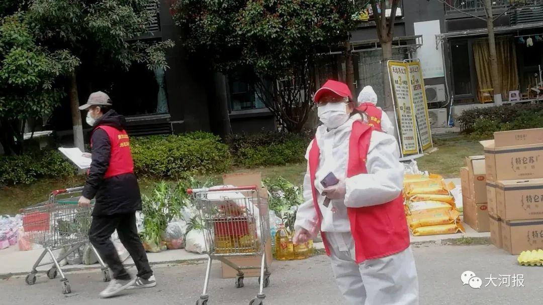 ▲小区外几位志愿者正在分拣整理蔬菜等物资