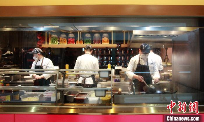 餐厅厨师戴口罩在厨房内做菜. 孟德龙 摄