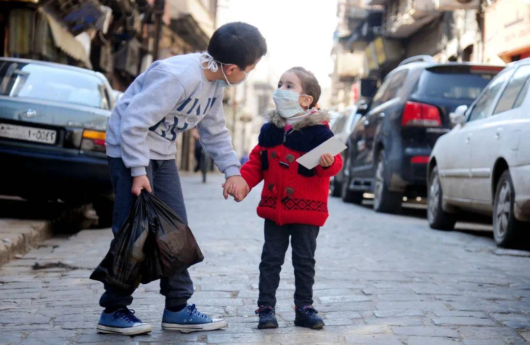 4月12日,在叙利亚大马士革,两名佩戴口罩的儿童走在街头。新华社发(阿马尔摄)