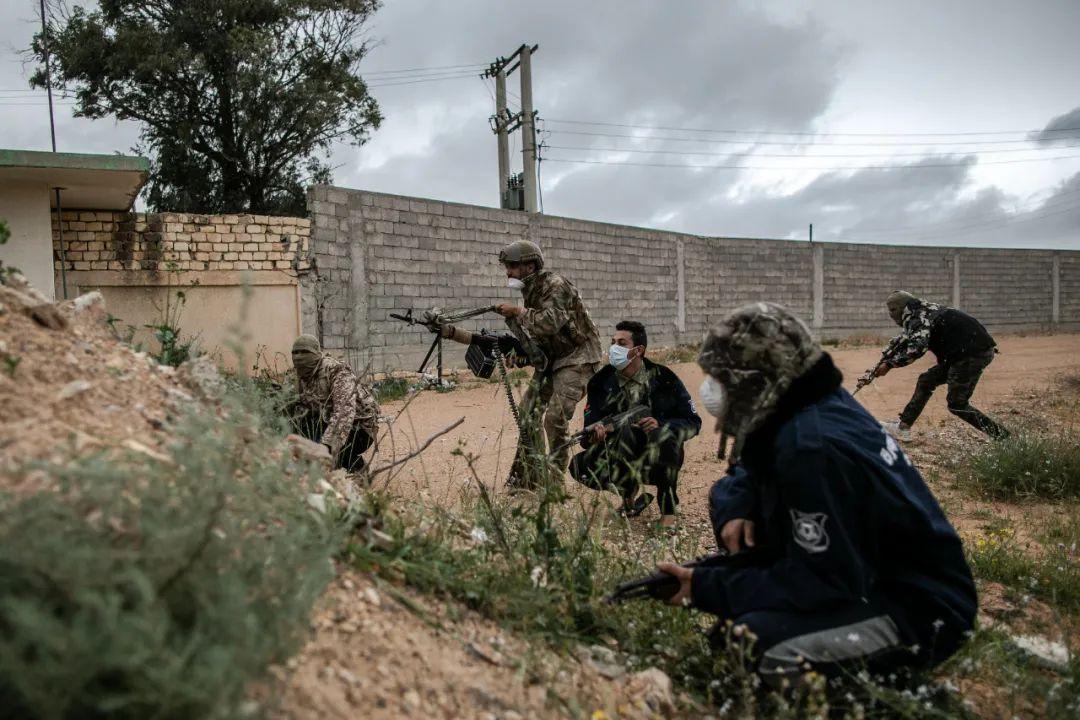 3月25日,在利比亚的黎波里,利比亚民族团结政府武装人员戴着口罩在战斗。新华社发(阿姆鲁摄)
