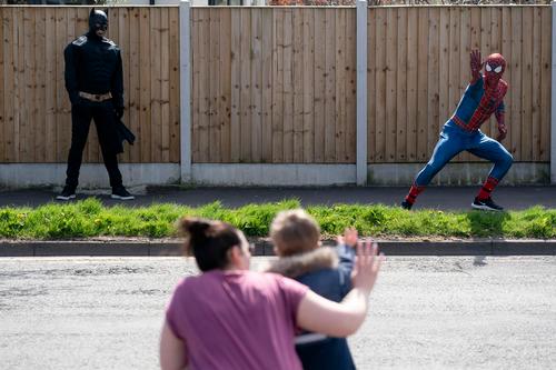"""4月13日,在英国曼彻斯特,打扮成""""蜘蛛侠""""的表演者来到居民区表演。新华社发"""