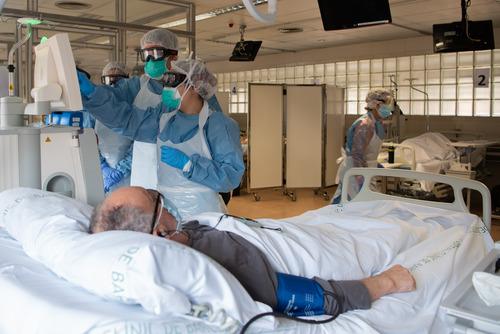 4月7日,在西班牙巴塞罗那医院,医务人员在病房内照顾新冠肺炎患者。新华社发