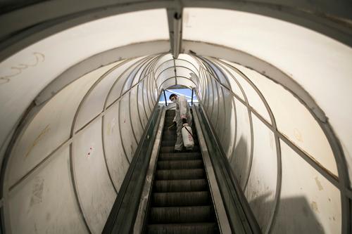 3月31日,在伊朗德黑兰,志愿者为扶手电梯消毒。新华社发(艾哈迈德·哈拉比萨斯摄)