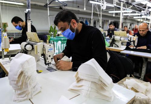 3月25日,在加沙城的一家工厂内,巴勒斯坦工人在生产医疗物资。新华社发