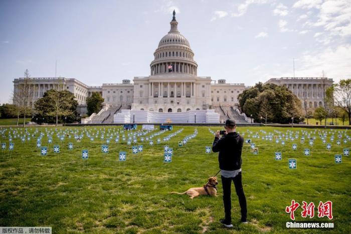 当地时间4月17日,新冠肺炎疫情期间,美国国会大厦西草坪上竖立起众多医疗工作者肖像照片,呼吁为医护提供个人防护设备。图为市民在照片上拍照。