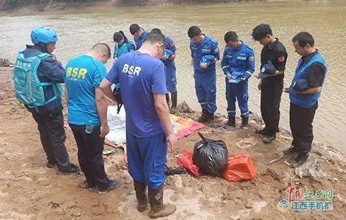图为救援人员向溺亡小孩默哀