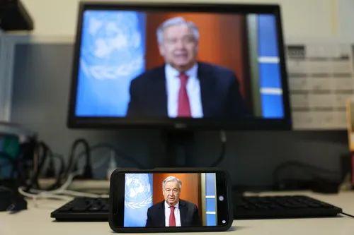 4月3日,在纽约的联合国总部,手机和电脑屏幕上播放联合国秘书长古特雷斯举行的视频记者会。新华社记者 谢锷 摄