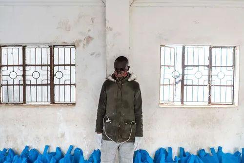 4月25日,在肯尼亚内罗毕的一个贫民区,一名工作人员准备发放救济物资。新华社/法新