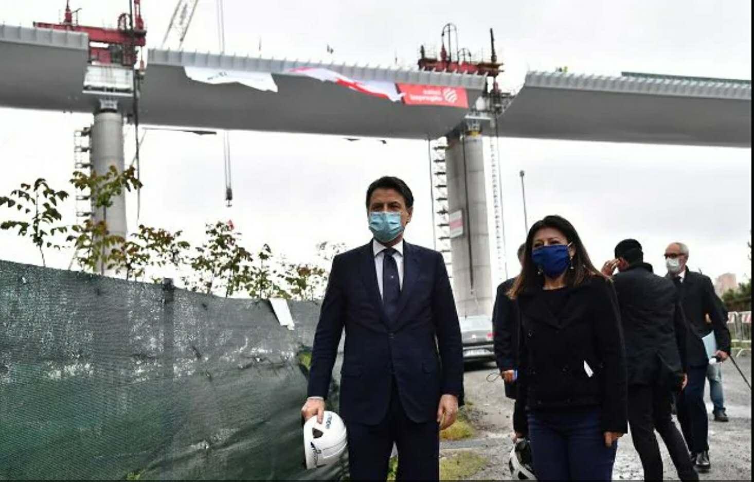 △意大利总理孔特(左一)出席大桥合龙仪式(图片来源:安莎社)