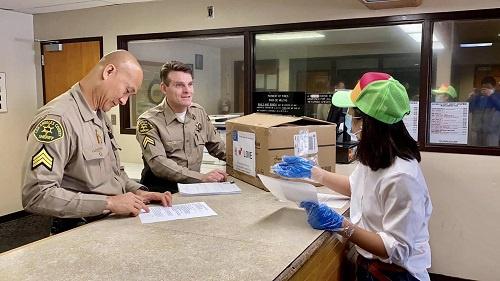 4月4日,在美国洛杉矶县,一名华人志愿者将捐赠的口罩送到当地警察局。 新华社发