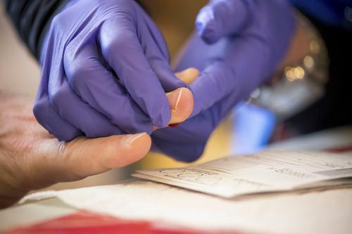 4月25日,在美国纽约布鲁克林区一家超市内的新冠抗体检测点,工作人员采集被测者血样。新华社发(郭克摄)