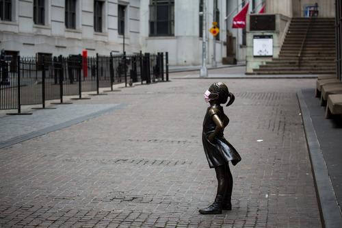 """4月27日,美国纽约证券交易所前被人戴上口罩的""""无畏女孩""""铜像。新华社发 (郭克摄)"""