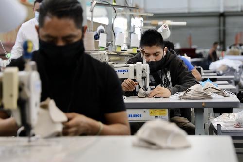 4月16日,工人在美国洛杉矶一家工厂缝制口罩。新华社发