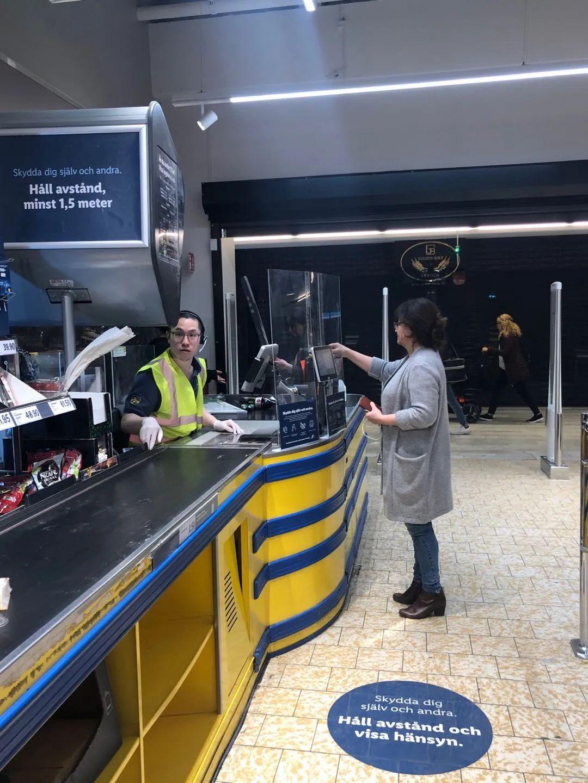 没戴口罩的超市收银员,其面前装有透明玻璃板以阻隔飞沫喷溅。
