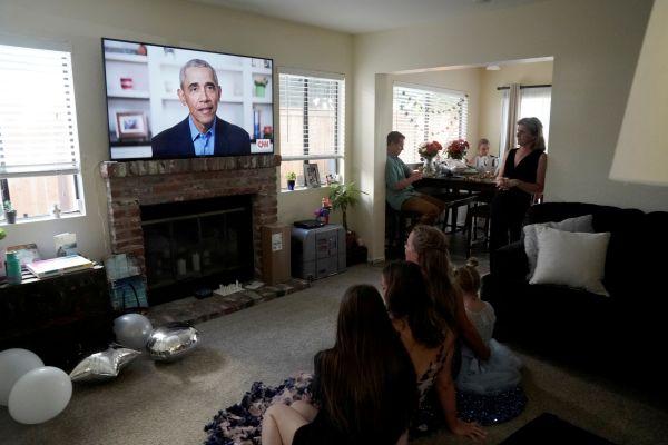 奥巴马16日在两场分别面向大学和高中毕业生的视频演讲中尖锐批评美国现政府抗疫不力。图为美国圣迭戈的高中生及其亲人16日在家观看奥巴马演讲。(路透社)