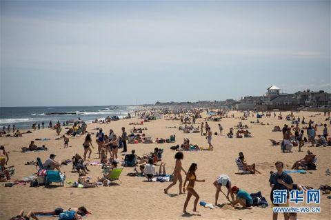 5月16日,人们在美国新泽西州贝尔马海滩享受阳光 图片来源:新华社