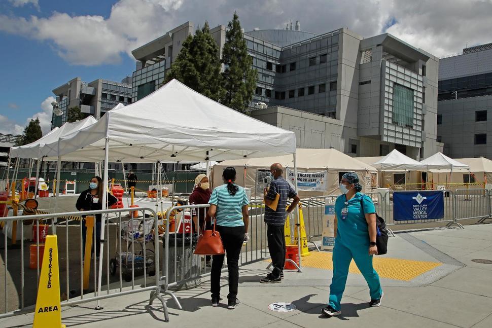 5月19日,美国加州圣何塞市,一名医护人员走过正在等待进行病毒检测的人群。(图源:美联社)