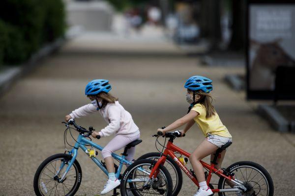 5月18日,两名美国儿童戴着口罩在骑车。新华社发