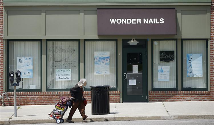 ▲资料图片:4月29日,在美国宾夕法尼亚州上达比,一名行人经过一家关闭的商店|新华社
