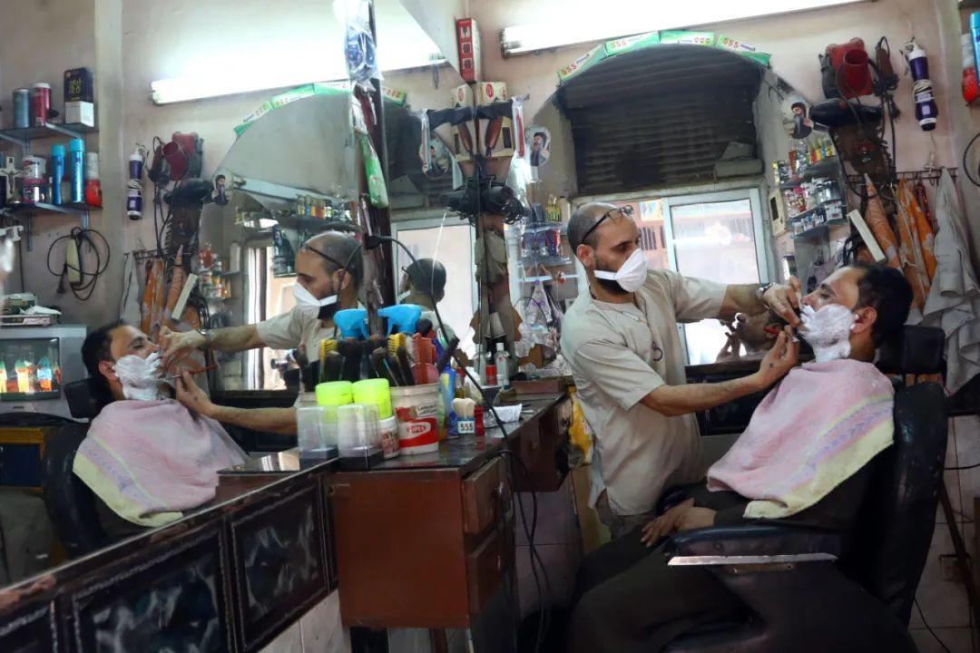 5月17日,在埃及开罗,一名戴口罩的理发师为顾客服务。新华社发(艾哈迈德·戈马摄)