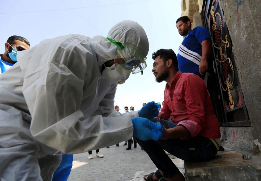 5月20日,在伊拉克巴格达市萨德尔城,医疗队员进行新冠病毒检测采样。新华社发(哈利勒·达伍德摄)
