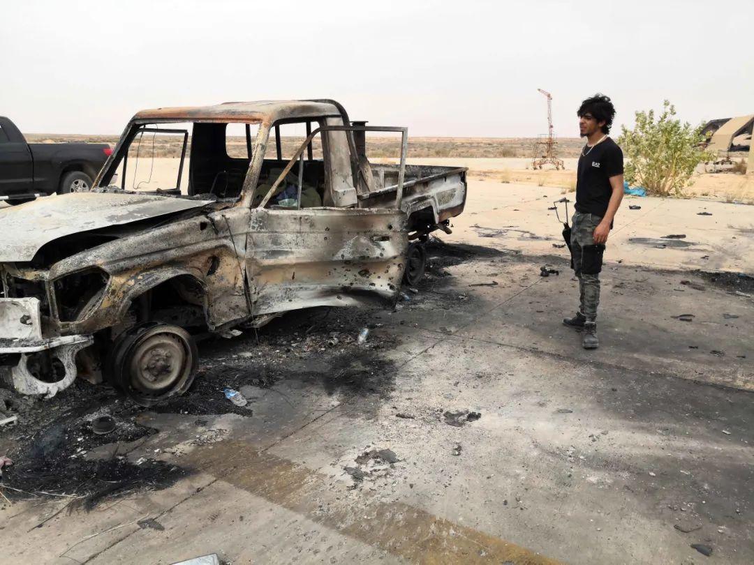 5月18日,在位于利比亚首都的黎波里西南约140公里处的瓦提耶空军基地,一名利比亚民族团结政府武装人员站在损毁的汽车旁。新华社发(哈姆扎·图尔基亚摄)